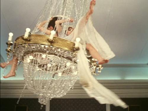 Woman Swinging From Chandelier
